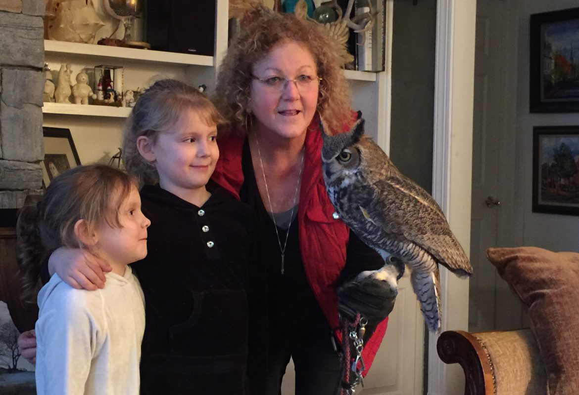 A woman holds an owl as two little girls look on in amazement.